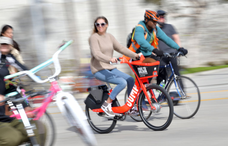 Image: A woman rides an Uber JUMP e-bike in Culver City, Calif.