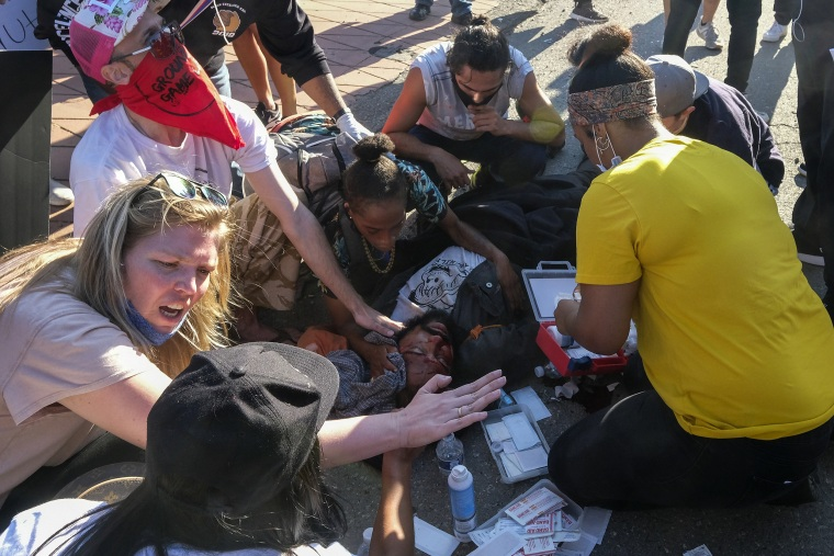 Demonstrators help a man who was sitting on a police car and injured by falling onto the ground during a protest to demand justice for George Floyd in downtown Los Angeles on May 27, 2020.