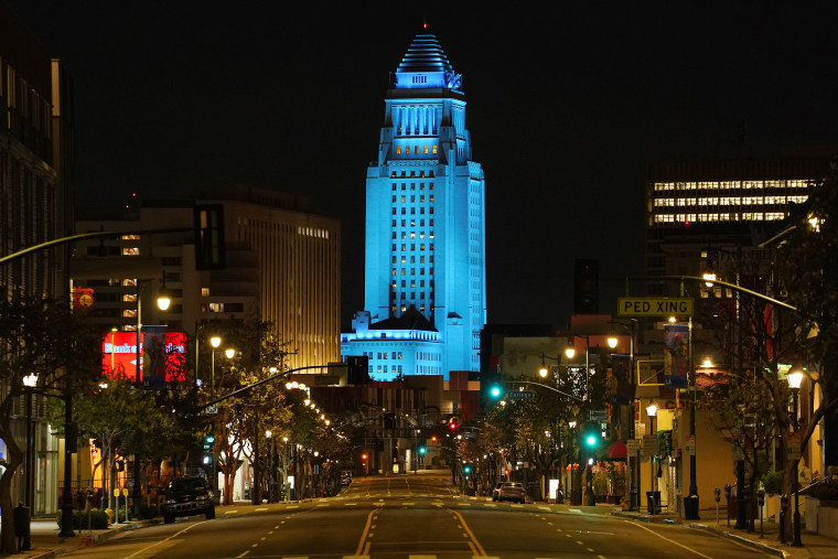 Los Angeles City Hall, seen lit up in blue to show support front line workers during the coronavirus pandemic, is ground zero for a massive bribery scandal unfolding in federal court.