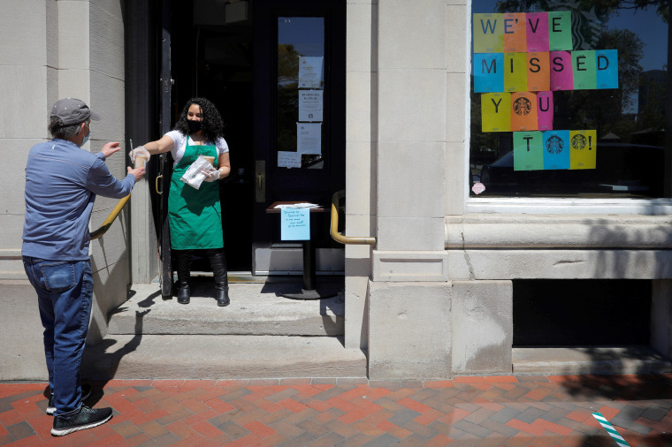 Image: A customer picks up an order at a reopened Starbucks in Boston on May 20, 2020.