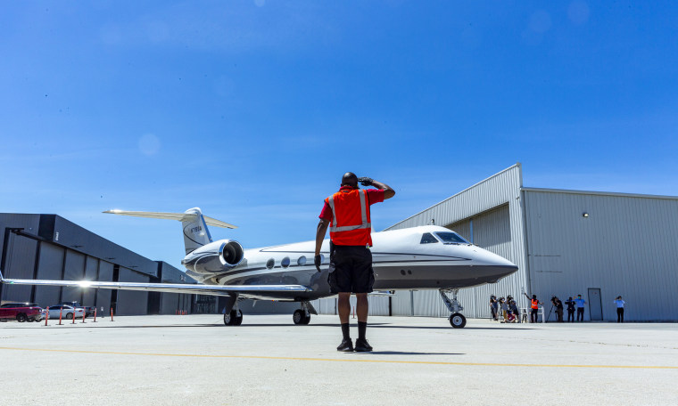 Image: A crew member salutes a Gulfstream IV jet carrying physicians on their way to New York from the Clay Lacy Aviation Terminal at Van Nuys Airport in Van Nuys, Calif., on April 23, 2020.