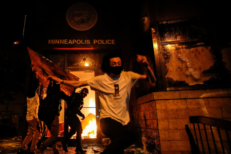 Image: Protesters react as they set fire to the entrance of a police station as demonstrations continue in Minneapolis