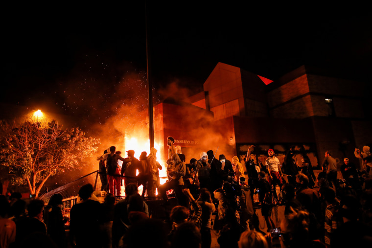 Image: Protesters gather around after setting fire to the entrance of a police station as demonstrations continue in Minneapolis
