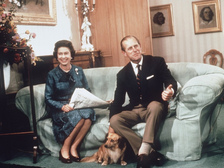 Image: Queen Elizabeth ll and Prince Phillip the Duke of Edinburgh relaxing with their corgis and newspapers at Balmoral