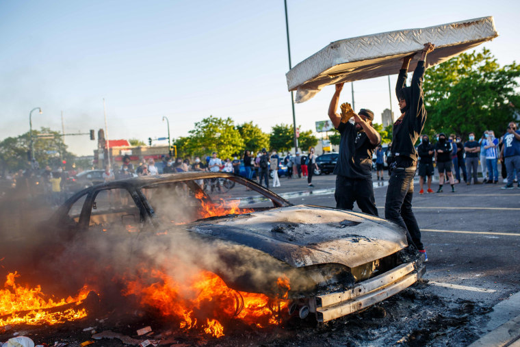 Protesters throw a mattress onto a burning car outside a Target store near the 3rd Precinct on May 28, 2020 in Minneapolis.