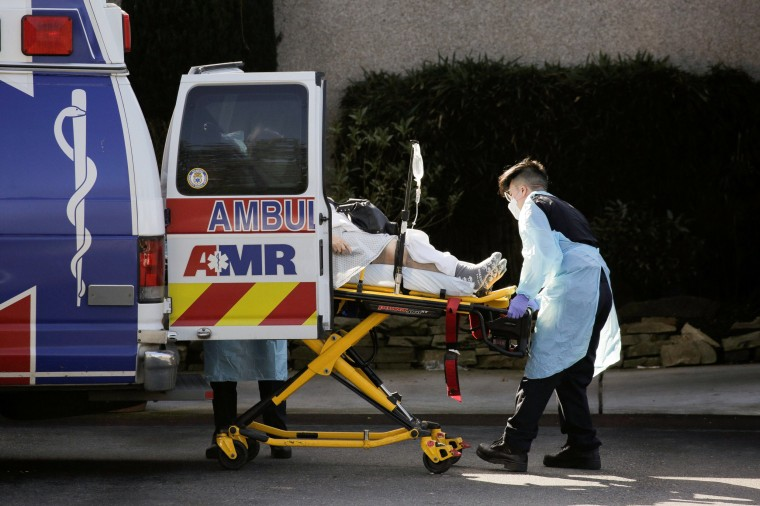 Image: Medics load a person into an ambulance the Life Care Center of Kirkland, the long-term care facility linked to several confirmed coronavirus cases in the state, in Kirkland