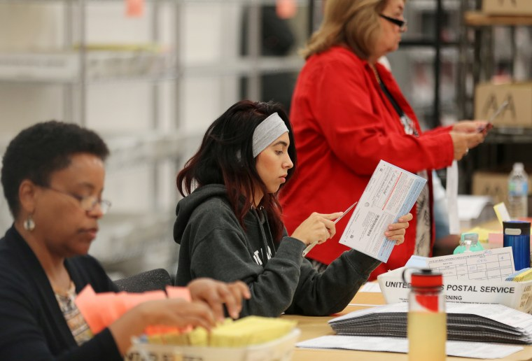 Election workers verify mail-in ballots in San Diego