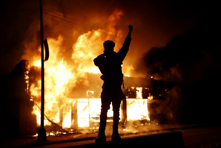 Image: A check-cashing business burns as a protester raises his fist in Minneapolis on May 29, 2020.