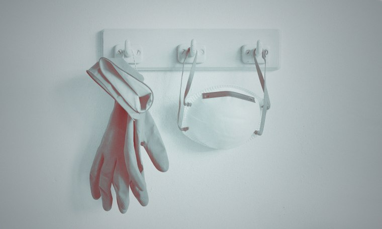 Still life of a face mask and protective gloves hanging at a coat hook
