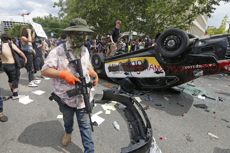 An armed protester walks past a flipped over police vehicle Saturday, May 30, 2020, in Salt Lake City.