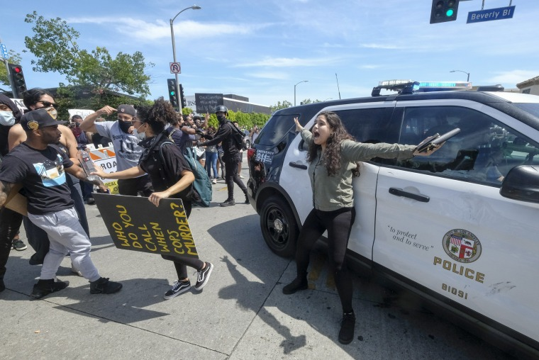 A protester tries to stop others from attacking a police vehicle in Los Angeles on May 30, 2020.