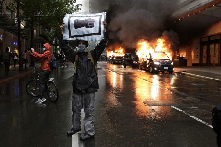 A man holds an image of a fist in front of burning vehicles in Seattle on May 30, 2020.