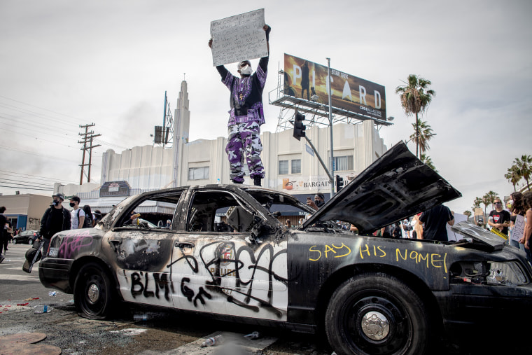 Image: A protester stands on top of a damaged police car in the Fairfax district of Los Angeles on May 30, 2020.