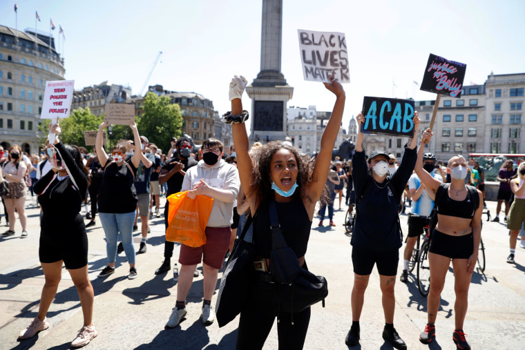 Image: People hold up signs during a protest in Trafalgar Square in London on May 31, 2020.