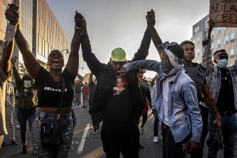 Image: A demonstrator wipes a tear from a fellow demonstrator's face during a clash with police officers as they protest the death of George Floyd and police brutality, in Minneapolis, Minn., on Friday, May 29, 2020. (Victor J. Blue/The New York Times)