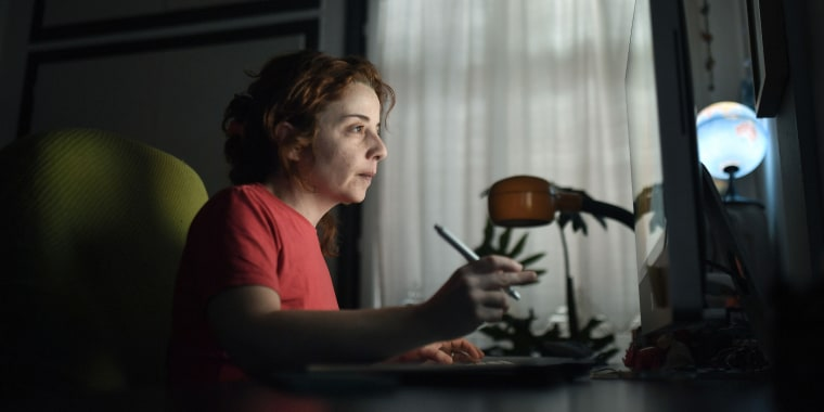 A woman works on her computer at her home office