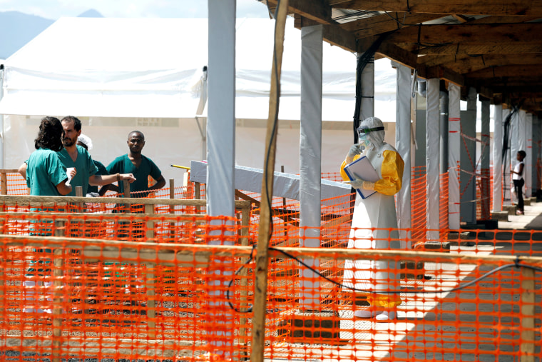 Image: FILE PHOTO: A health worker dressed in a protective suit talks to medical staff at the newly constructed MSF Ebola treatment centre in Goma