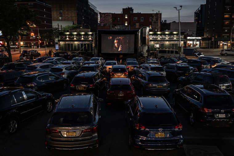 """Patrons watch \""""The Greatest Showman\"""" at the Bel Aire diner parking lot in Queens, N.Y., on May 25, 2020. The diner in Astoria created a drive-in movie theater in the parking lot behind the restaurant with room for 45 socially distanced cars."""