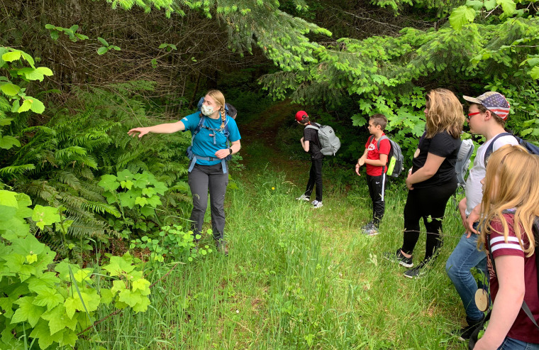 Campers and a counselor in a face mask go on a socially-distanced nature hike at Camp Wilani in Veneta, Oregon. The camp just hosted its first campers of the COVID-19 era last week.