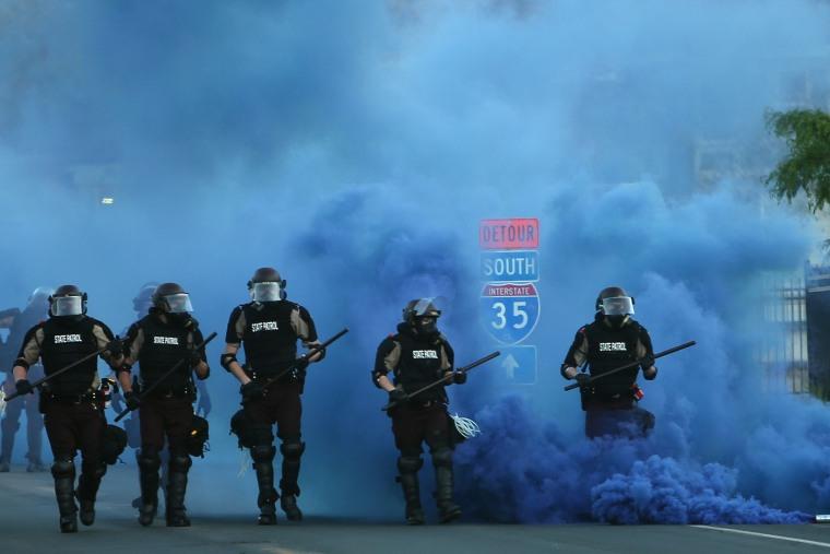 Police advance on demonstrators Saturday in Minneapolis.