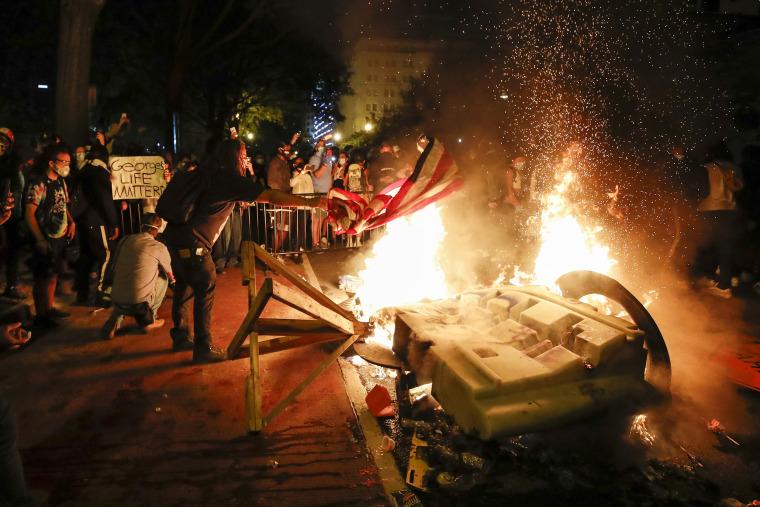 Image: Demonstrators start a fire