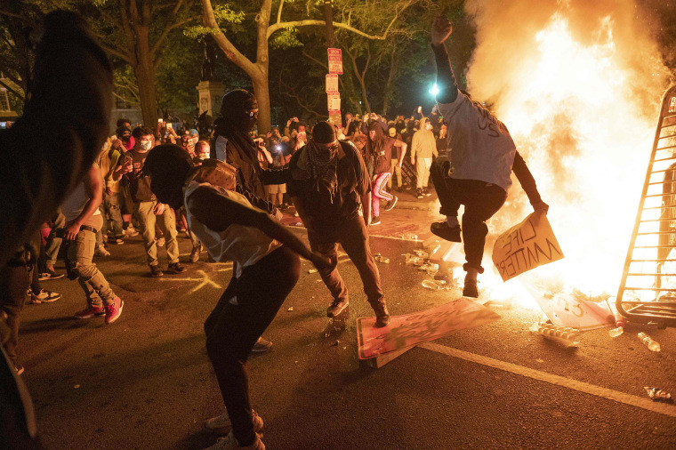 Image: Protesters jump on a street sign near a burning barricade during a demonstration against the death of George Floyd near the White House