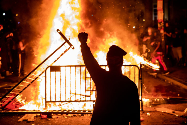 Image: A protester raises a fist near a fire during a demonstration outside the White House over the death of George Floyd at the hands of Minneapolis Police in Washington