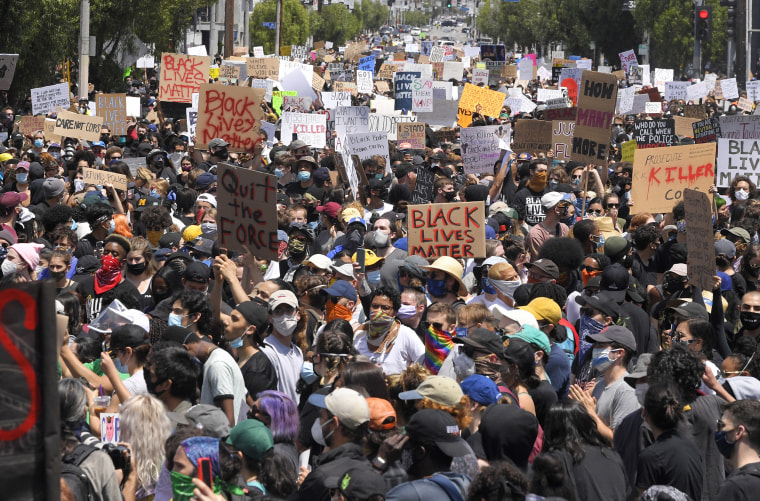 Demonstrators sit in an intersection during a protest in Los Angeles on Saturday, May 30, 2020, over the death of George Floyd.