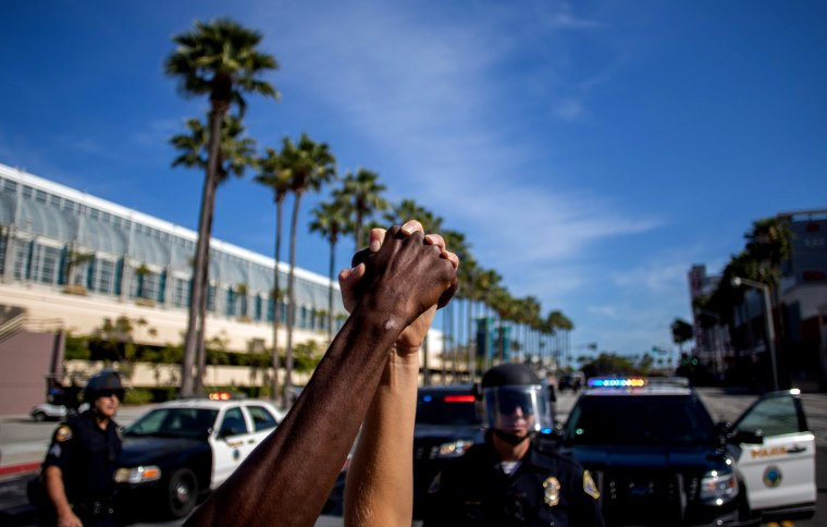 Image: People hold hands in solidarity during a protest demanding justice in the death of George Floyd in Long Beach, Calif., on May 31, 2020.
