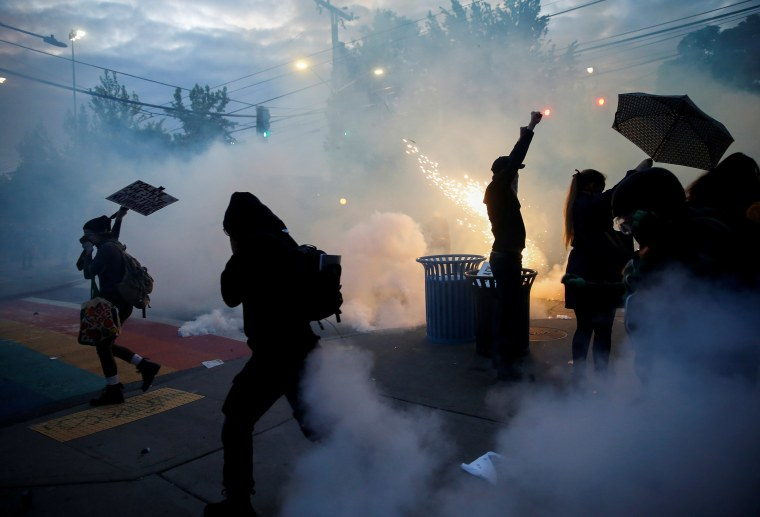 Image: Protesters disperse as tear gas, pepper spray and flash-bang devices are deployed by Seattle police during a protest against police brutality and the death in Minneapolis police custody of George Floyd, in Seattle