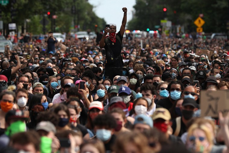 Image:  A man holds up his fist while hundreds of demonstrators march to protest against police brutality and the death of George Floyd, on June 2, 2020