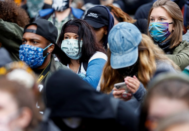 """Image: A protester wears a surgical mask with \""""Black Lives Matter\"""" written on the front while protesters gather outside the Seattle Office of Emergency Management to protest against police brutality and the death in police custody of George Floyd"""