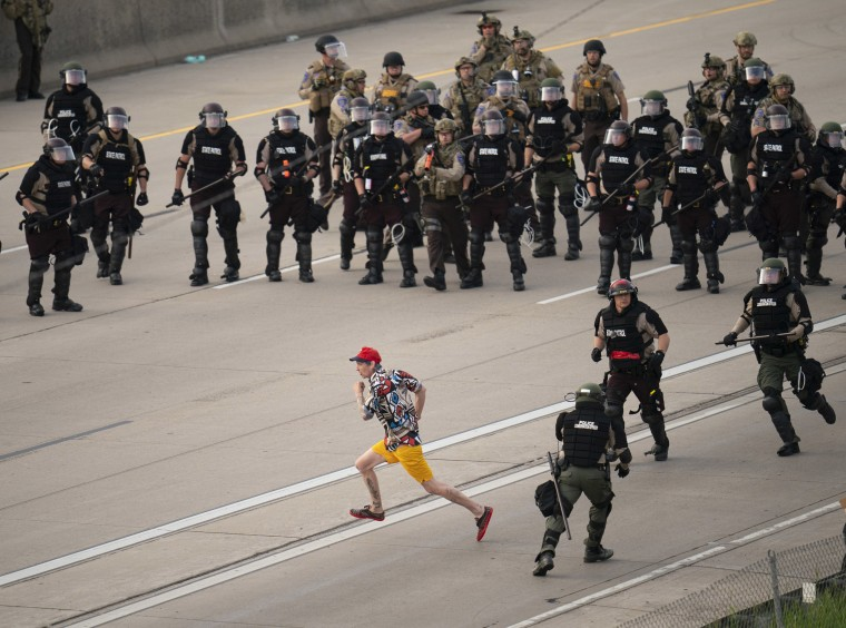 A protester tries to elude police officers as they try to disperse people during a protest in Minneapolis on May 31, 2020.