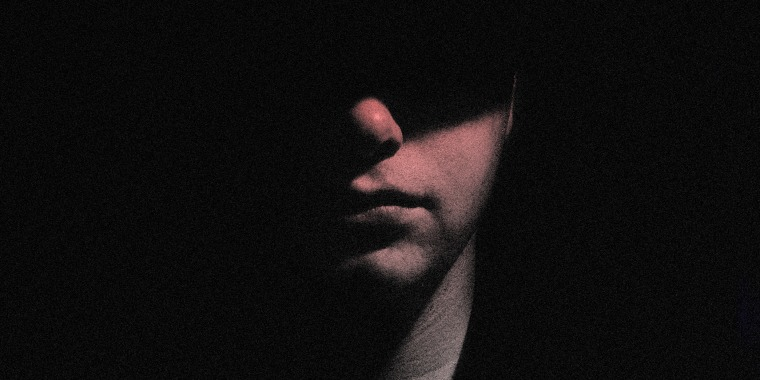 Image: Portrait of a man with half of his face hidden in shadow.