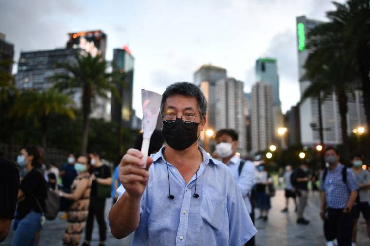 Image: A man holds up a candle in remembrance outside Victoria Park in Hong Kong