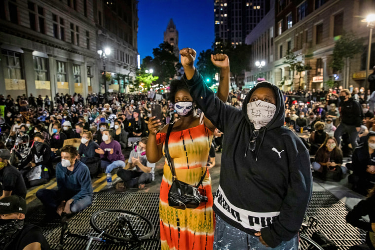 """Demonstrators raise their fists during a """"Sit Out the Curfew"""" protest in Oakland, Calif. on June 3, 2020."""