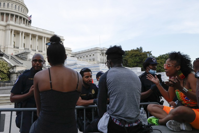 Image: U.S. Capitol police officers talk with demonstrators as they have a conversation about racism in America as they protest the death of George Floyd
