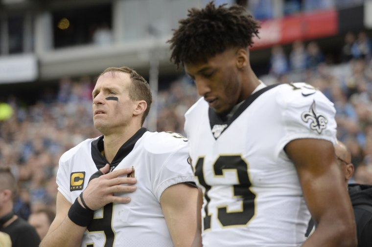 New Orleans Saints quarterback Drew Brees and wide receiver Michael Thomas stand for the national anthem before in Nashville, Tenn., on Dec. 22, 2019.