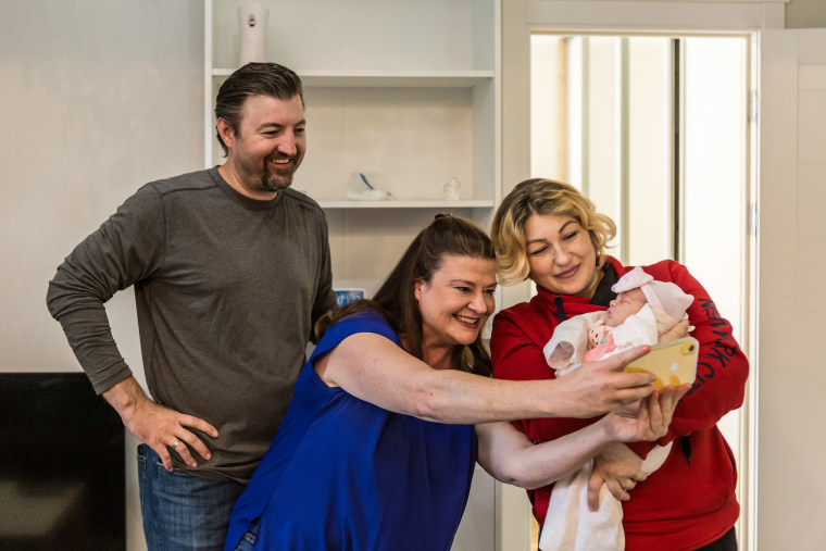 Image: Darlene Straub, 45, center, takes a selfie with Yulia, 33, left, a surrogate mother from Vinnytsia region holding Straub's newbron daughter Sophia, right, and her husband Chris Straub, 43, in Kyiv