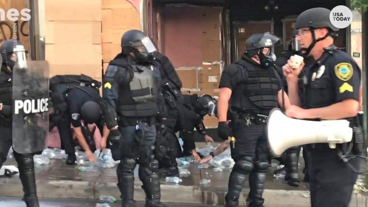 Police officers destroy water bottles at a medic tent set up for protesters in Asheville, N.C., on June 2, 2020.