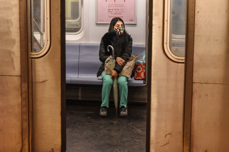 A passenger wears a mask while riding on a New York City subway train on May 6, 2020.