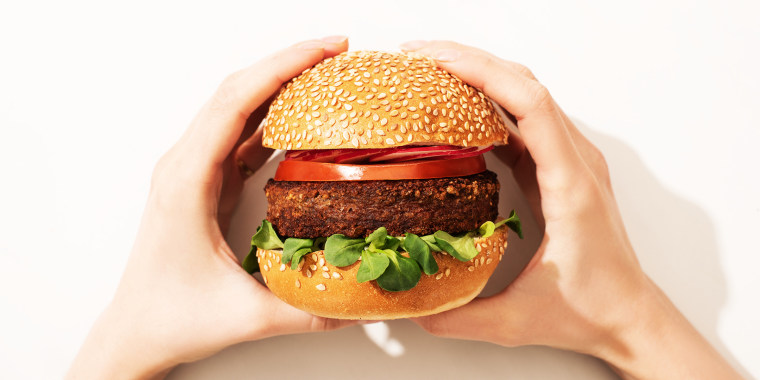 cropped view of woman holding delicious vegan burger with radish on white background
