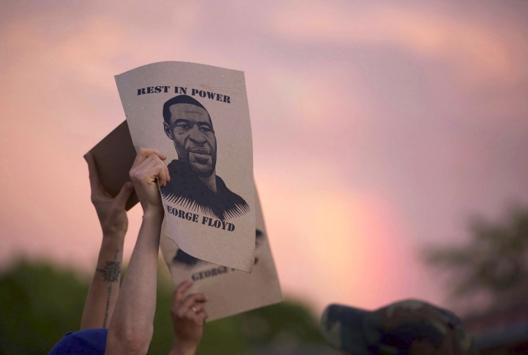A protester holds a sign with an image of George Floyd during protests on May 27, 2020, in Minneapolis.