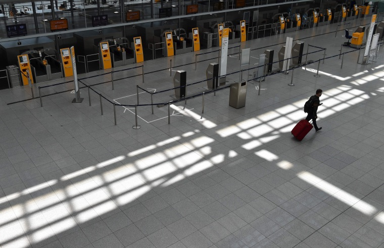 "Image: A passenger walks in an empty terminal at the ""Franz-Josef-Strauss"" airport in Munich"