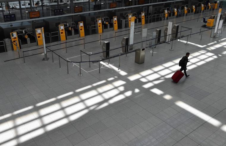 "Image: A passenger walks in an empty terminal at the \""Franz-Josef-Strauss\"" airport in Munich"