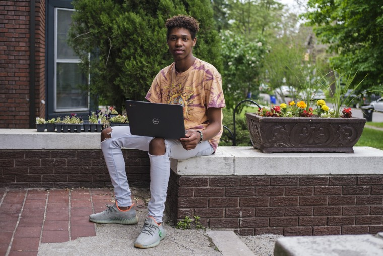 Xavier Prater, 17, a Grosse Pointe South High School student, with his laptop outside his father's home in Detroit.