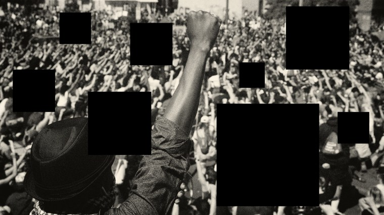 Image: A protester raises his fist while surrounded by black squares.