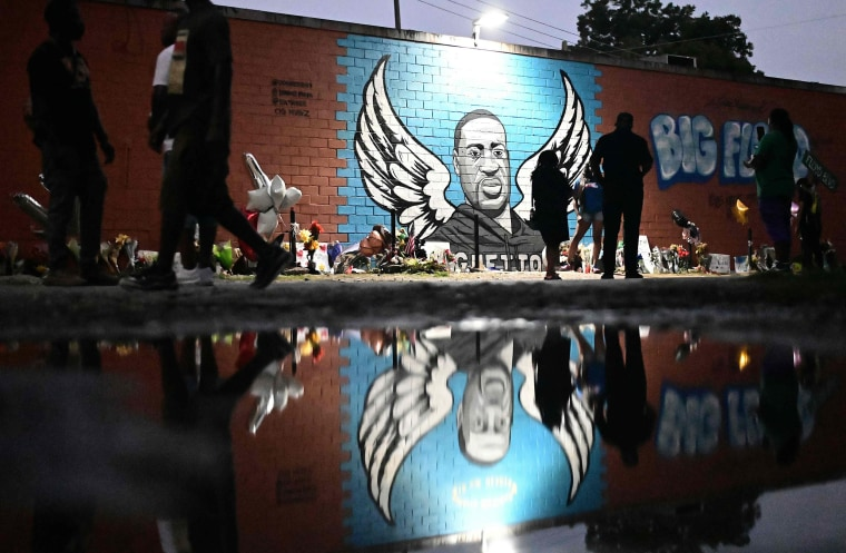 Image: People stand in front of a mural of George Floyd in Houston