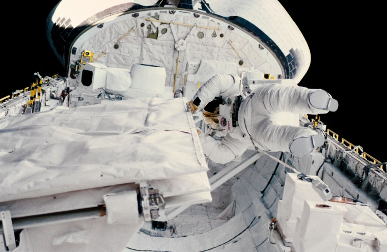 Astronaut Kathryn D. Sullivan checks the latch of the SIR-B antenna in the space shuttle Challenger's open cargo bay during her historic extravehicular activity (EVA) on Oct. 11, 1984.