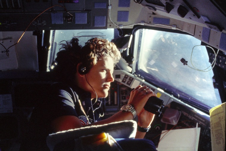 Astronaut Kathryn D. Sullivan, 41-G mission specialist, uses binoculars for a magnified viewing of Earth through Challenger's forward cabin windows on Oct. 6, 1984.
